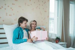 namorado surpreende a namorada com caixa de presente na cama foto
