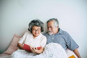 casal de idosos deitado na cama lendo um livro foto