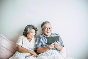casal de idosos usando um computador tablet foto