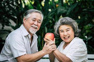 casal de idosos brincando e comendo frutas