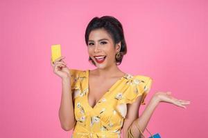 mulher elegante com sacolas de compras e cartão de crédito foto