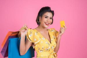 mulher elegante com bolsa de compras e cartão de crédito foto