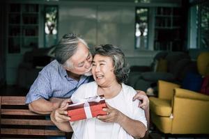 marido sênior sorridente fazendo surpresa dando uma caixa de presente para sua esposa foto