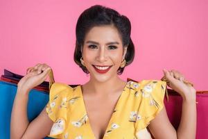 linda mulher asiática segurando sacolas coloridas foto