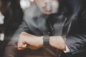 jovem empresário sentado no café, olhando para o relógio