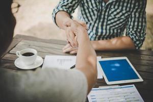close-up de dois executivos apertando as mãos enquanto está sentado no local de trabalho foto