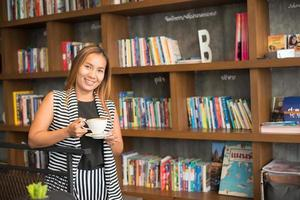 mulher asiática relaxando com um café no café foto
