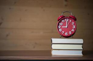 despertador às 9h na pilha de livros na mesa de madeira