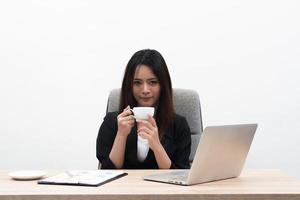jovem empresária asiática com notebook no escritório isolado no fundo branco foto