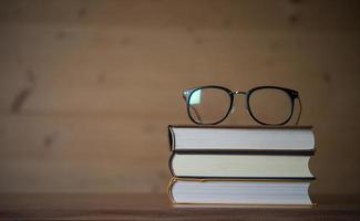 copos na pilha de livros na mesa de madeira