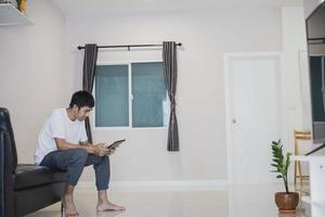 homem asiático segurando o tablet em casa no sofá