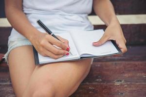 bela jovem escrevendo no bloco de notas enquanto está sentado no banco