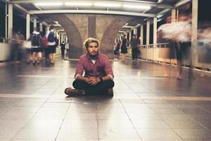 homem barbudo hipster sentado no chão enquanto viaja à noite foto