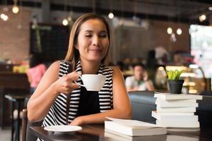mulher asiática relaxando e lendo um livro no café foto