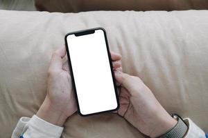 pessoa segurando um telefone celular com tela em branco foto