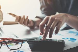 close-up de um contador usando uma calculadora foto