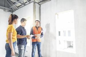 três pessoas construindo uma casa