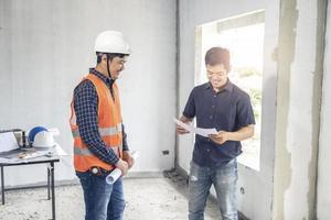 dois inspetores examinando planos de construção