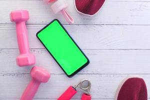 telefone inteligente com equipamento desportivo no chão de madeira foto