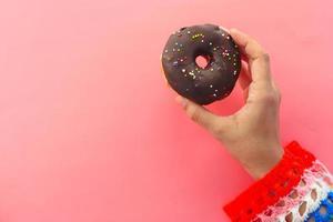 mulher segurando um donut no fundo rosa foto