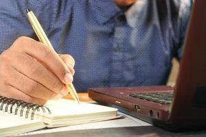 feche a mão do homem escrevendo em um caderno