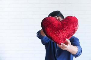 homem segurando um travesseiro de lantejoulas coração foto