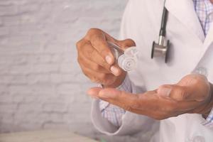 mão do médico usando gel desinfetante