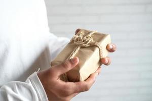 mão de homem segurando uma caixa de presente com espaço de cópia