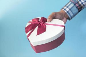 mão de homem segurando uma caixa de presente em forma de coração foto