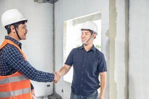 dois jovens engenheiros apertando as mãos