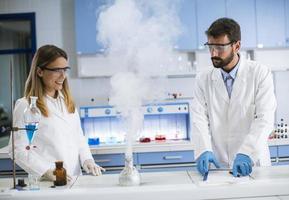 pesquisadores fazendo experimentos com fumaça em uma mesa de um laboratório químico foto