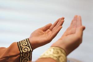 mãos de uma mulher muçulmana ou islâmica gesticulando enquanto orava em casa foto