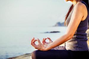 mulher meditando em uma praia tropical