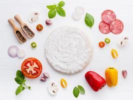 massa de pizza rodeada de ingredientes frescos foto