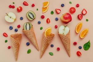 cones de waffle e frutas em um fundo marrom foto