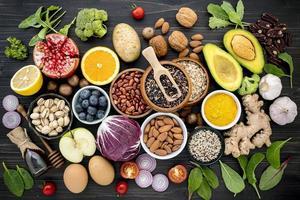 alimentos frescos saudáveis em um fundo escuro de madeira foto