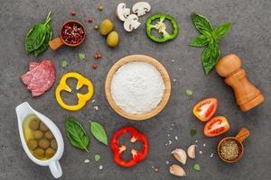 ingredientes frescos de pizza em um fundo cinza escuro
