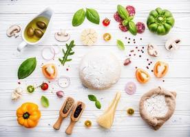 ingredientes frescos de pizza em um fundo branco surrado foto