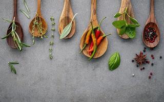 especiarias e ervas em colheres de madeira em um fundo cinza foto