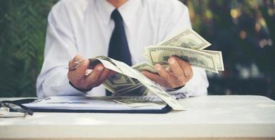 empresário sênior contando notas de dólar foto