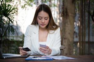 mulher segurando um cartão de crédito e usando um telefone inteligente para fazer compras online com um tom vintage foto