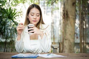 jovem empresária sentada em um escritório tomando uma xícara de café foto