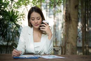 jovem empresária sentada em um escritório bebendo uma xícara de café foto
