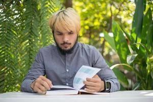 jovem hippie barbudo lendo livros no jardim doméstico com a natureza foto