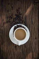 vista superior da xícara de café e grãos de café na mesa de madeira