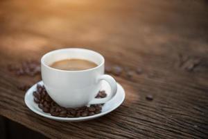 xícara de café e grãos de café na mesa de madeira foto