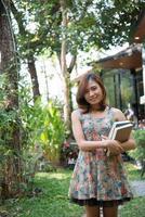 jovem feliz em pé e segurando cadernos na horta foto