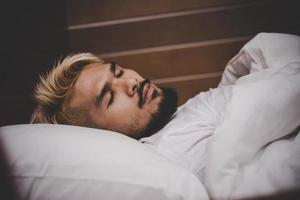 belo jovem barbudo dormindo foto