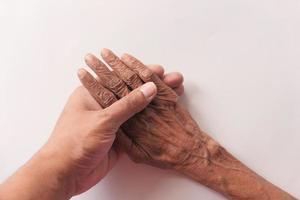 jovem segurando a mão de um idoso