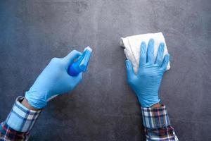 mãos com luvas de borracha azuis segurando um frasco de spray